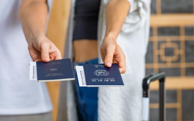 Крупным планом: паспорт германии и республики корея с утверждением сертификата карты учета вакцинации против коронавируса covid-19 в руках путешественницы перед иммиграционной службой на размытом фоне.