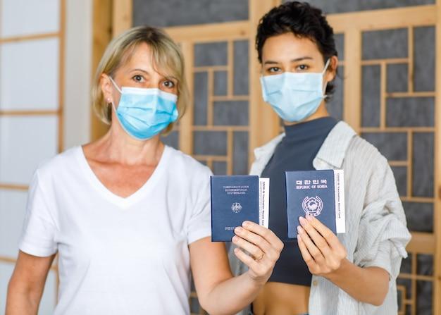 ぼやけた背景でフェイスマスクを着用している白人の金髪とアジアの女性の手でcovid-19ワクチン接種記録カード証明書とドイツと韓国のパスポートのクローズアップショット。