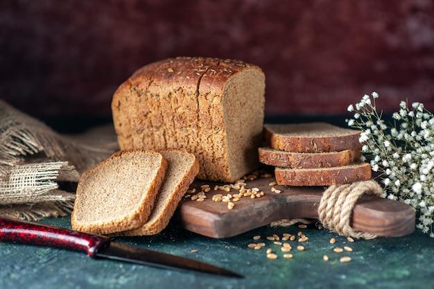 混合色の背景に木製まな板ナイフ花茶色のタオルの上の食餌療法の黒いパン小麦のショットをクローズアップ