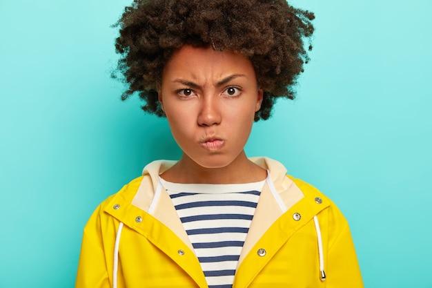 アフロの髪型、怒りで顔を眉をひそめ、悪い秋の天候に悩まされ、縞模様のジャンパーと黄色の防水レインコートを着て、青で隔離された不機嫌な若い女性のクローズアップショット