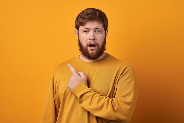 Крупным планом эмоциональный шокированный бородатый молодой мужчина широко открывает рот и смотрит в камеру
