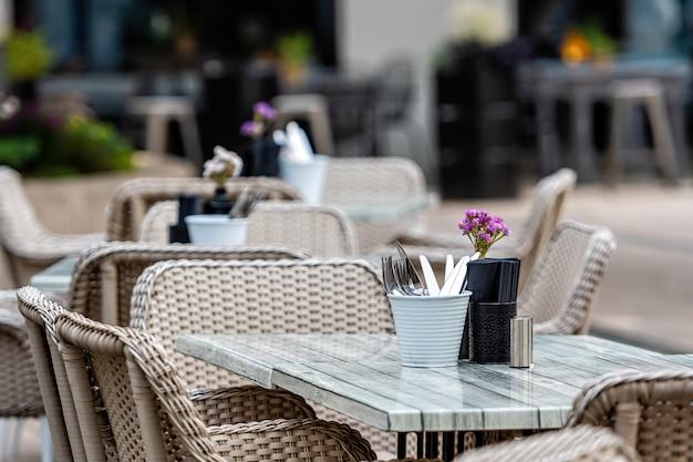 通りの椅子と空の食堂やレストランのテーブルのショットを閉じる
