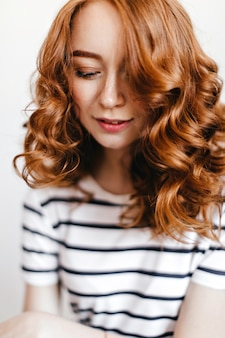 빛나는 물결 모양의 머리를 가진 매혹적인 여성 모델의 클로즈업 샷. 눈으로 포즈 유행 백인 여자의 실내 사진을 폐쇄.