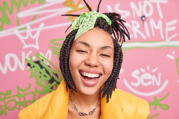 ストリートスタイルで広く服を着た民族の10代の少女の笑顔のクローズアップショットは、若者のギャングの一部である落書きの壁に対して優しいドレッドヘアの髪型のポーズを持っています