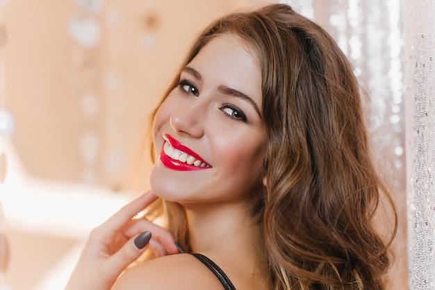검은 곱슬 머리와 은색 벽에 웃 고 저녁 화장 유럽 여자의 클로즈업 샷.