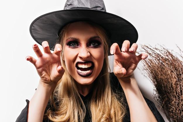 회색 눈을 가진 사악한 마녀의 클로즈업 샷입니다. 검은 모자에 무서운 여성 뱀파이어의 실내 사진.
