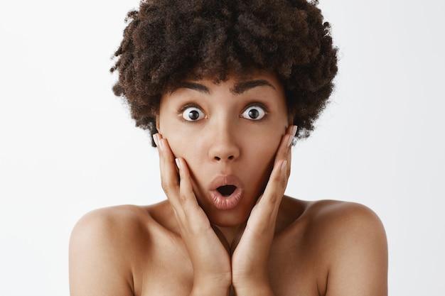 興奮して驚いて驚いたかわいい裸のアフリカ系アメリカ人女性のクローズアップショット。