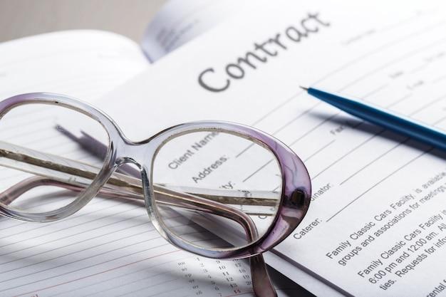 Закройте вверх по съемке eyeglasses на концепции дела документов контракта