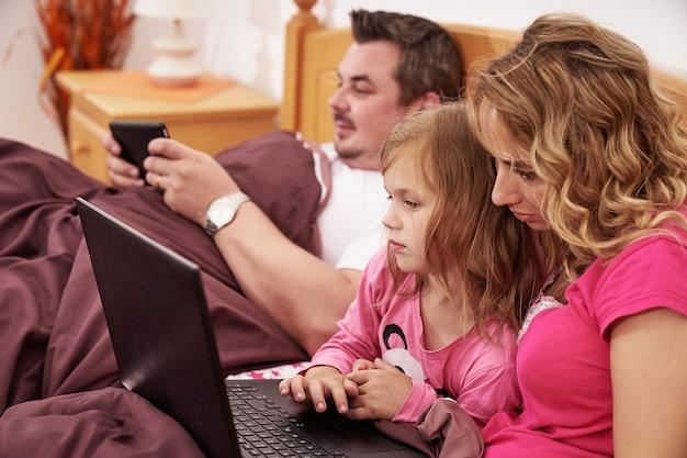 朝ベッドに横たわっている間にデジタルデバイスを使用して家族のショットをクローズアップ