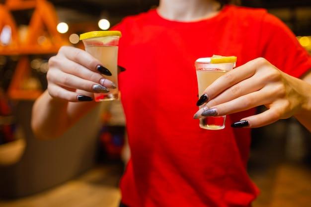 バーでのパーティー中にカクテルのグラスで乾杯する女性の友人のクローズアップショット。