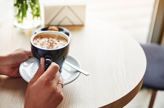 カプチーノとセラミックの青いカップを保持している女性の手のクローズアップショット。コーヒー休憩時間。スペースをコピーします。食べ物や飲み物の概念