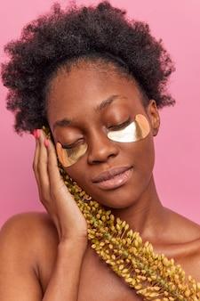 Снимок крупным планом, женщина-модель держит дикое растение возле лица, применяет золотые патчи от мешков под глазами, чтобы уменьшить мелкие морщинки, стоит без рубашки, изолированной над розовой стеной
