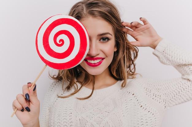 Крупным планом женская модель с красной помадой, держащей леденец на белой стене