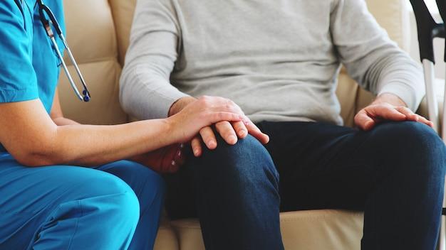 요양원의 소파에 앉아 있는 동안 노인의 손을 잡고 있는 여성 간호사의 사진을 클로즈업합니다. 간병인 및 사회 복지사