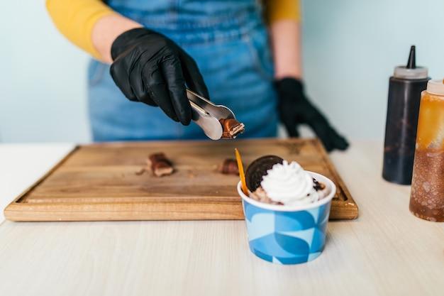 手作りのアイスクリーム店で働く女性労働者の手のショットをクローズアップ。