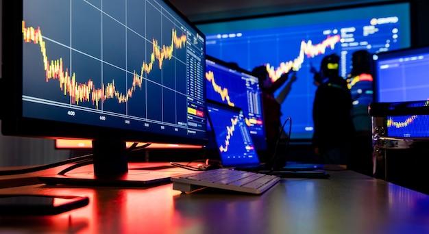 Крупным планом снимок финансового анализа диаграммы диаграммы фондовой биржи биткойн криптовалютный отчет на мониторах экрана компьютера и ноутбуке на работе в торговой комнате во время встречи брокера в тени позади.