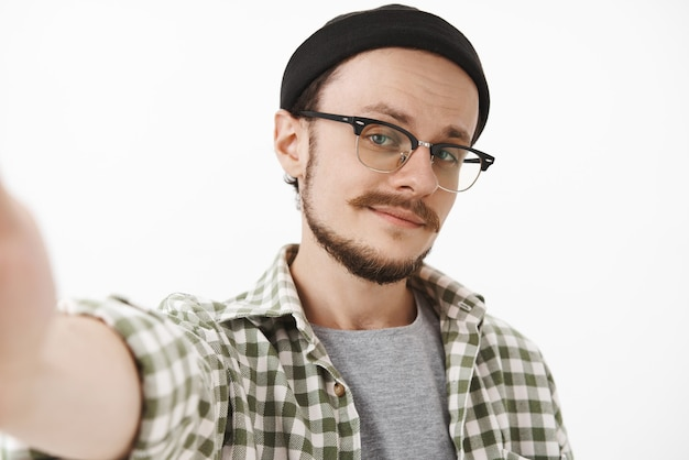 Крупным планом кокетливый самоуверенный молодой красавец с бородой в черной стильной шапке и клетчатой рубашке, делающий селфи