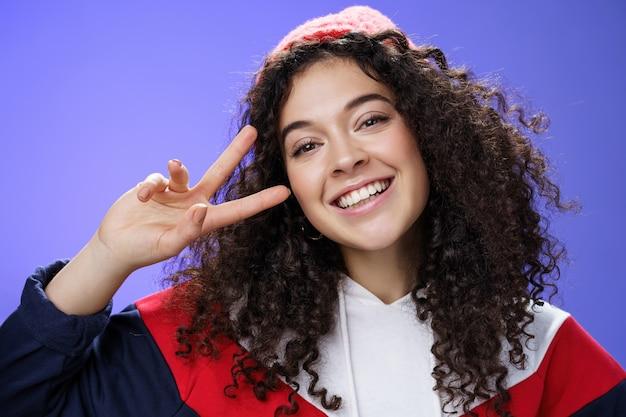 温かいビーニーが頭を傾けて、顔の近くで勝利または平和のジェスチャーを示して喜んで笑い、青い壁の上で幸せと喜びを感じている、フレンドリーで魅力的な縮れ毛の女性のクローズアップショット。