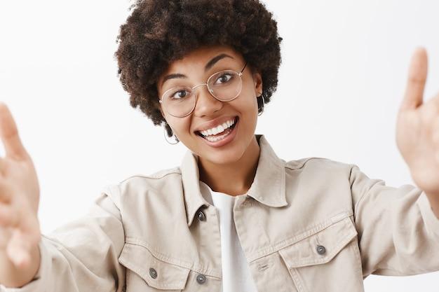 フレンドリーな感情的でかわいいアフリカ系アメリカ人女性のクローズアップショット。透明なメガネとシャツの手を引いて、selfieを取り、頭を傾け、新しい写真をオンラインで広く投稿して笑っています。
