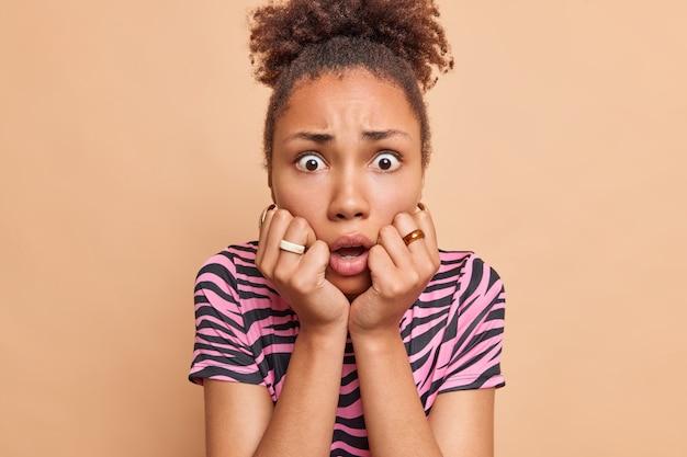 おびえた心配している縮れ毛の民族女性のクローズアップショットは、茶色の壁にさりげなく隔離された服を着て恐怖から震える神経質な怖い表情で顎の凝視の下に手を保ちます