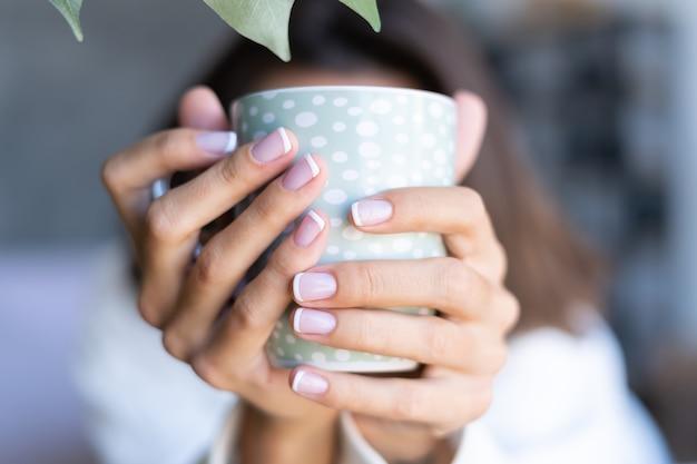 Крупным планом снимок руки девушки, держащей кружку кофе дома с идеальным французским маникюром