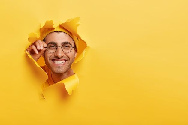 嬉しい白人男性のクローズアップショットは、眼鏡の縁に手を置いています