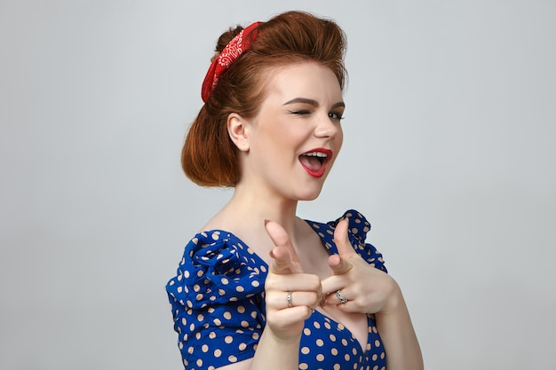 Крупным планом снимок гламурной привлекательной молодой брюнетки в винтажном платье в горошек, мигающей и указывая указательными пальцами