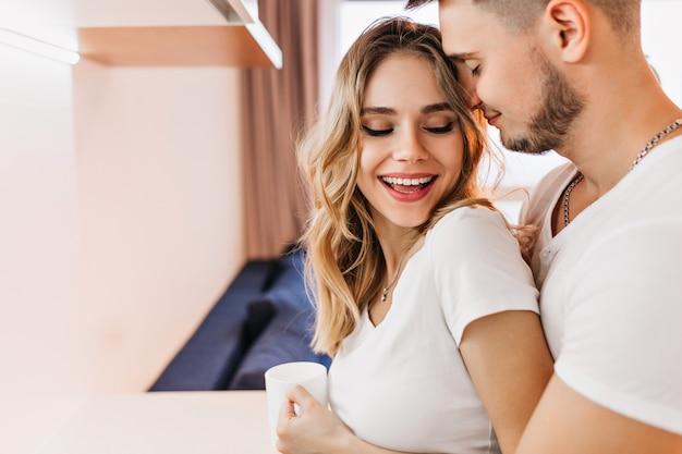 남편에 게 웃 고 차 한잔과 함께 좋은 기분 좋은 여자의 클로즈업 샷. 남자 친구와 함께 커피를 즐기는 금발 곱슬 여자의 실내 사진.