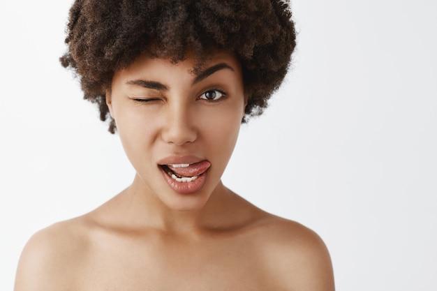 見栄えのする軽薄で官能的な女性のホットな女性が裸でポーズをとって、舌を見せて誰かを誘惑しているようにウインクしているクローズアップショット