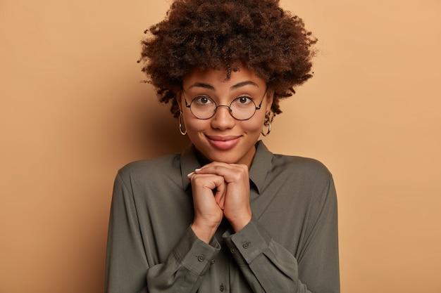 잘 생긴 여자의 클로즈업 샷은 건강한 피부를 가지고 있고, 손을 턱 아래에 유지하고, 침착하게 카메라를 응시하고, 둥근 안경과 셔츠를 입습니다.