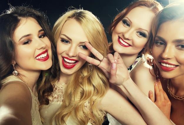パーティーをしている笑っている女の子のグループのクローズアップショット、スマートフォンで自分撮りを撮る