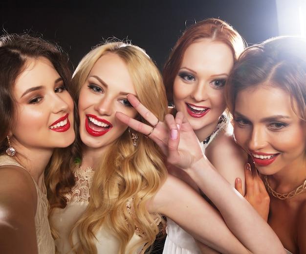 Снимок крупным планом группы смеющихся девушек, устраивающих вечеринку, делающих селфи со смартфоном