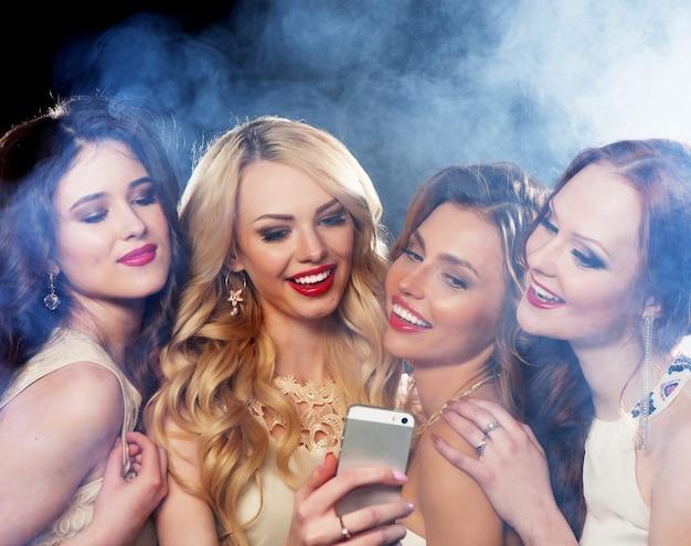 파티를 하는 웃고 있는 소녀 그룹의 클로즈업 샷, 스마트폰으로 셀카 찍기