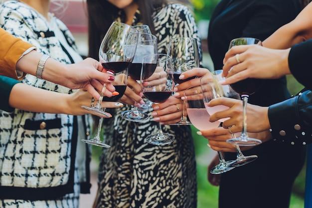 ボケ味の背景の前でワインやシャンパンとグラスをチリンと鳴らす人々のグループのクローズアップショット。高齢者の手。
