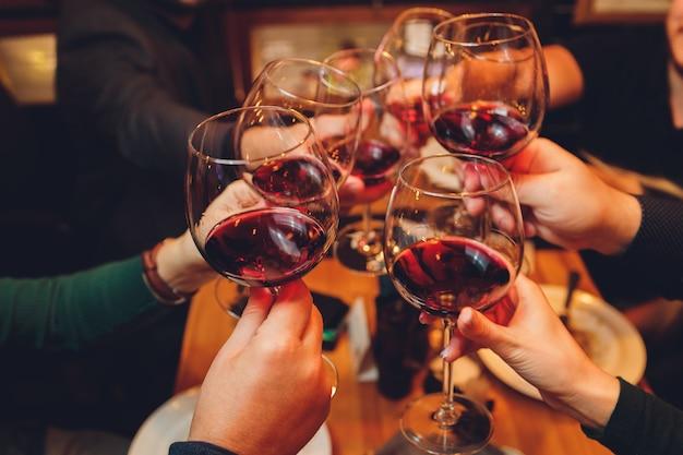 ボケの前でワインやシャンパンとグラスをチリンと鳴らす人々のグループのクローズアップショット