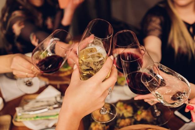 Крупным планом снимок группы людей, звенящих бокалами с вином или шампанским перед боке