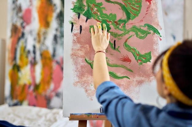 作成中に指でキャンバスにペイントを適用する女性アーティストの手のショットをクローズアップ