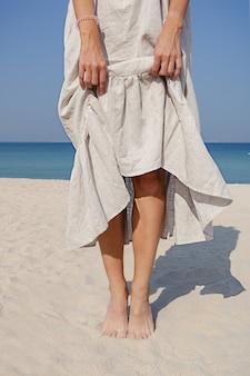 砂の海のビーチで裸足で立っている長いリネンのドレスを保持している女の子の手のショットをクローズアップ