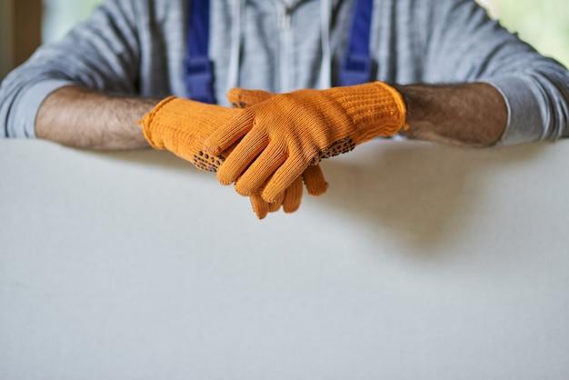 주택 건설 작업을 하는 동안 건식 벽체를 들고 보호 장갑을 끼고 남성 건축업자의 손을 클로즈업