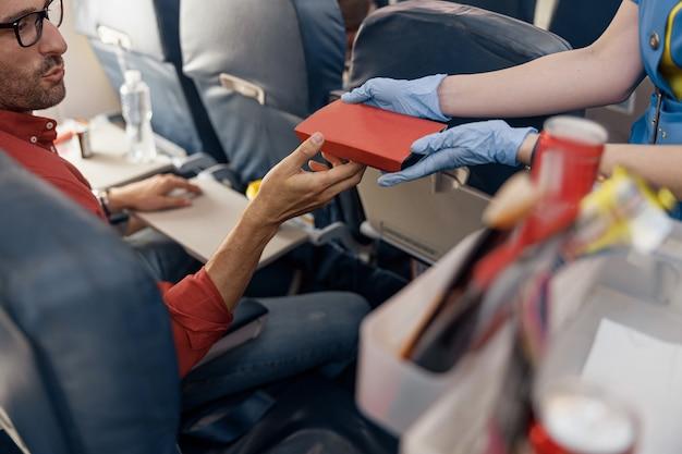 Крупным планом руки пассажира-мужчины, получающего ланч-бокс от бортпроводницы, подающей еду