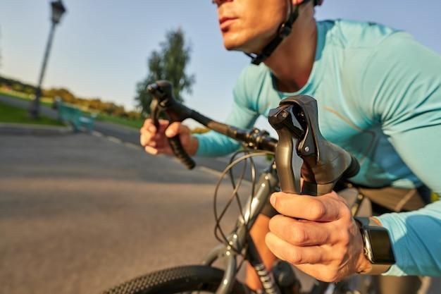 Крупным планом выстрел из рук на руле профессионального велосипедиста, езда на своем шоссейном велосипеде в парке.