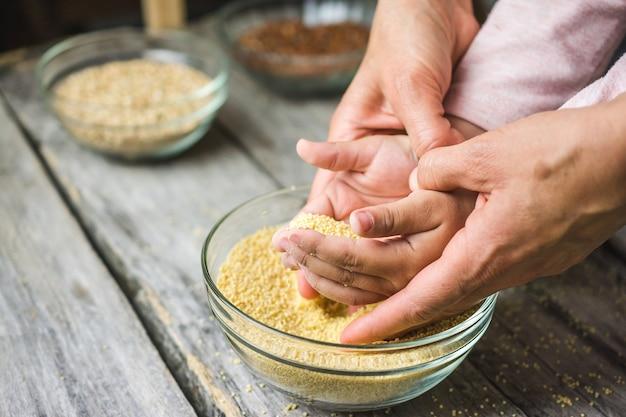 新鮮な全体のアマラス穀物ボウルに入れられた手のショットをクローズアップ