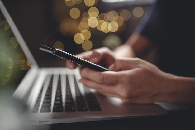 ノートパソコンで検索するためのスマートフォンのタイピングメッセージを使用して手のショットを閉じる