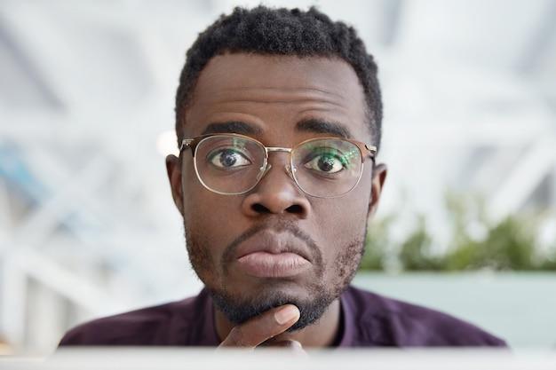 어두운 순수한 피부를 가진 잘 생긴 아프리카 아메리카 남성의 총을 닫고 둥근 안경과 공식적인 옷을 입습니다.
