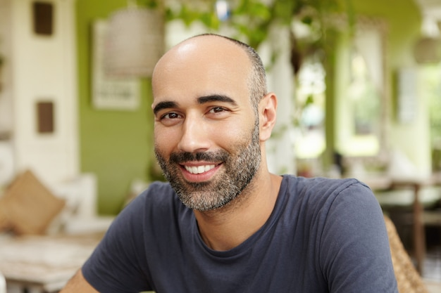 Крупным планом снимок красивого кавказского человека с бородой, одетого в футболку, смотрящего и улыбающегося со счастливым жизнерадостным выражением лица, сидящего в ресторане на тротуаре в солнечный день и ожидающего друзей