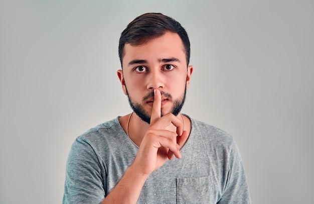 Shhhジェスチャーでハンサムな男性のクローズアップショット、沈黙を求めて、または静かにする、灰色の背景で隔離