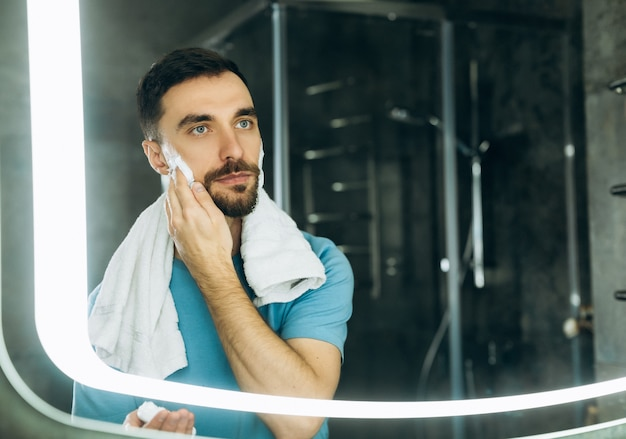 거울 앞에 서서 그의 얼굴에 면도 거품을 적용하는 그의 목에 수건으로 잘 생긴 젊은 남자의 근접 촬영