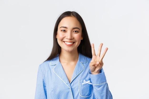 Крупным планом счастливая привлекательная азиатская женщина в синей пижаме, показывающая три пальца и улыбающиеся белые зубы, объясняющая основные правила или делая порядок, стоя на белом фоне в восторге.