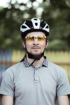 보호용 헬멧과 노란색 선글라스를 쓰고 수염을 가진 행복 한 매력적인 젊은 남자의 총을 닫습니다.