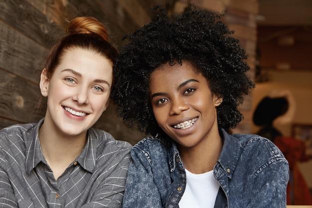Закройте снимок счастливой красивой рыжей женщины, расслабляющейся в кафе со своей стильной афро-американской подругой